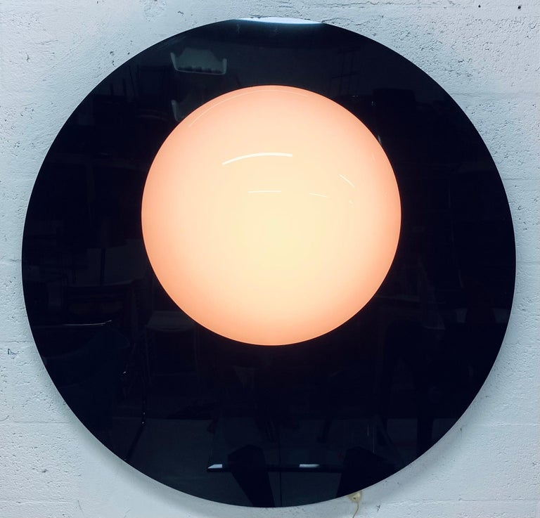 Black and white moulded plexiglass wall mounted lamp sculpture that resembles a lunar eclipse from the 1980s. Can be mounted four ways (see images).