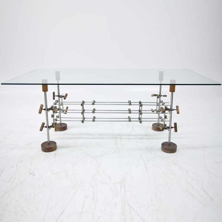 Table on round wooden discs, with unusual steel frame made of individual struts and fixings in the form of clamps. Glass table top.