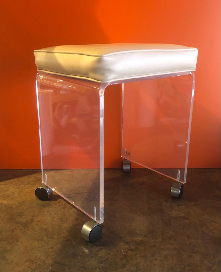Postmodern waterfall Lucite vanity stool or bench by Akko, circa 1970s. The bench has a cream colored Naugahyde seat and is in good vintage condition; very solid and stabile. There some scratches, crazing and fogging to the Lucite. #1298.