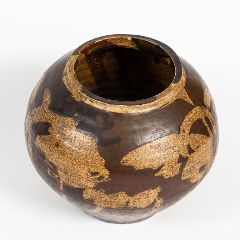 This is a small ceramic pot dating from turn of the century France. It features an abstract pattern in neutral tones of brown. It measures 7.5 in in diameter and 6.5 in tall.