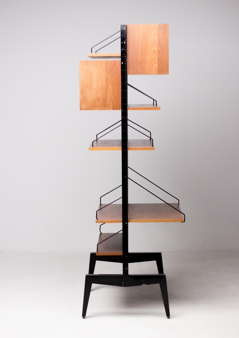 This is a very practical free standing teak shelving system with desk by Paul Cadovius. You can arrange it anyway you like. The picture shows just one possible set up. Featuring 2 posts, 2 glass door cabinets, 4 shelves and 1 tabletop. Very good