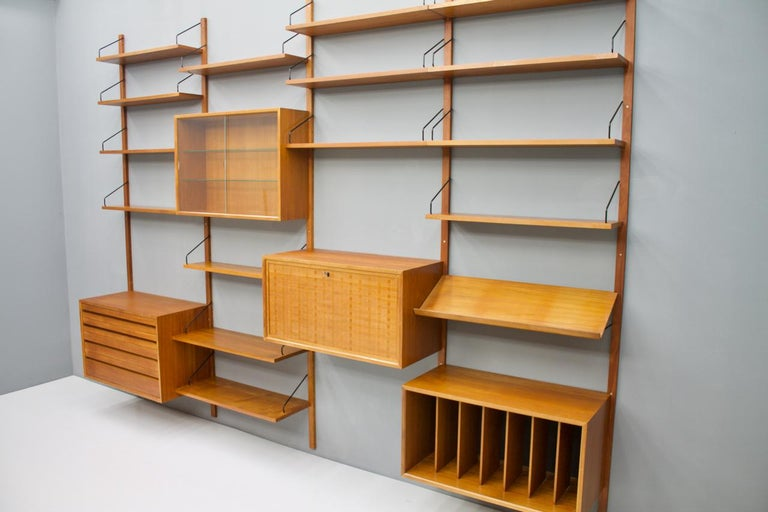 Large teak wood wall system 'Royal' by Poul Cadovius for Cado, Denmark 1956  1 x teak cabinet with 4 drawers 1 x teak vitrine with two glass doors  1 x teak cabinet, desk 1 x Teak cabinet 2 x shelves 80 x 30 cm.  13 x shelves 80 x 20 cm.  1