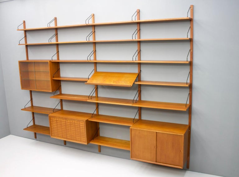 Large teak wood wall system 'Royal' by Poul Cadovius for Cado, Denmark, 1956 1 x teak cabinet with 2 sliding doors 1 x teak vitrine with two glass doors 1 x teak cabinet, dry bar 4 x shelves 80 x 30 cm. 16 x shelves 80 x 20 cm. 1 x magazine