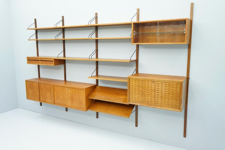 Large teak wood wall system 'Royal' by Poul Cadovius for Cado, Denmark 1956  1 x teak cabinet / desk with on front door 1 x teak vitrine with two glass doors 1 x teak cabinet, bar with one door 1 x teak cabinet with two sliding doors 1 x small