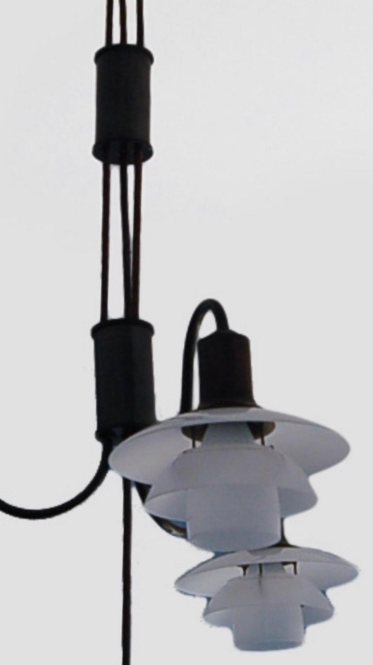 An early and rare Poul Henningsen (Ordrup, Denmark 1894-1967) adjustable-height 4 lamp chandelier. The cylindrical canopy has a suspending two height-adjusting cylinders of patinated brass connected by PH brown cloth cords with three (3) graceful