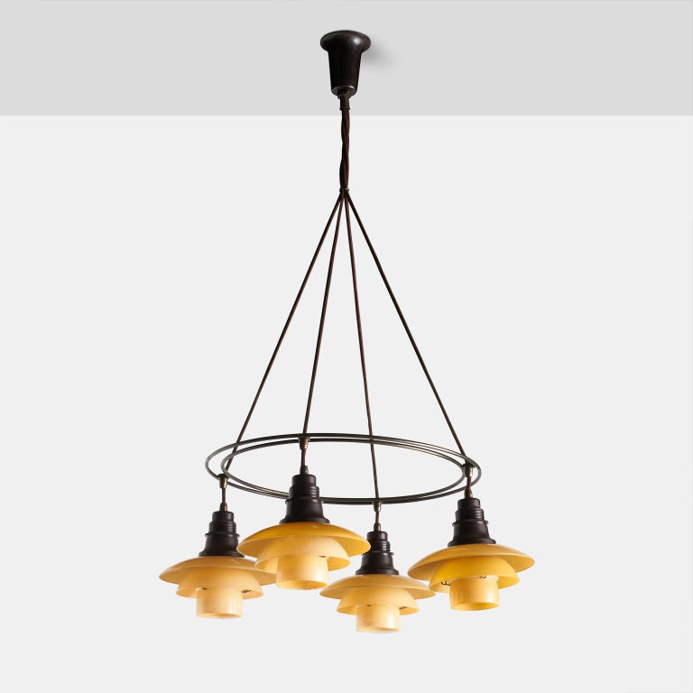 A double ring chandelier by Poul Henningsen. Features a browned brass frame, four shades of 2/2 yellow/matte glass with bakelite socket covers and wire holders. Stamped
