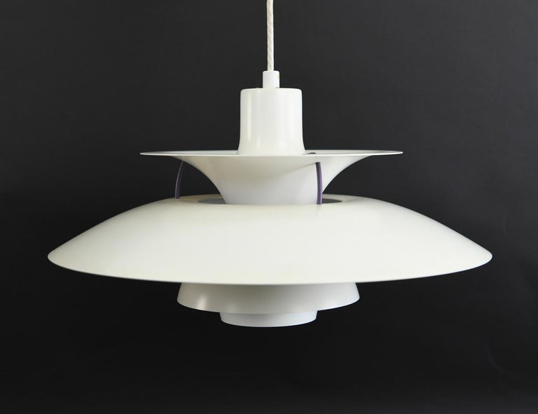 This timeless Danish midcentury pendant light is Poul Henningsen's 1958 design for Louis Poulsen which has been frequently reproduced due to high demand. Henningsen's clever design uses blue and red interior components that bring a warmer light when