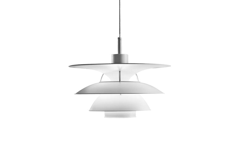The trumpet-shaped top shade provides illumination of the area above the three lower shades, which primarily direct the light downwards. A base reflector and a blue glare ring protect against glare from all angles. The strongest light is directly