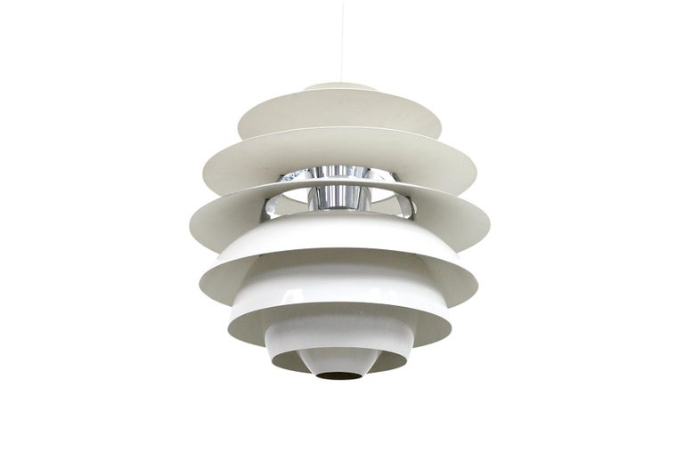 Snowball pendant designed in 1924 by Poul Henningsen for the Danish lighting company Louis Poulsen. Architectural louvered design emits indirect light that fills the room with ambient illumination.