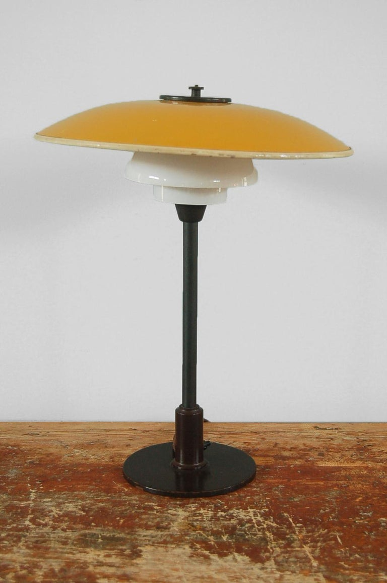 Poul Henningsen (1894 Ordrup, Denmark - Hillerød, Denmark 1967), table light 3/2 yellow or white metal top shade with opal white glass middle and lower shades, patinated metal components, manufactured by Louis Poulsen, Copenhagen, Denmark, origin: