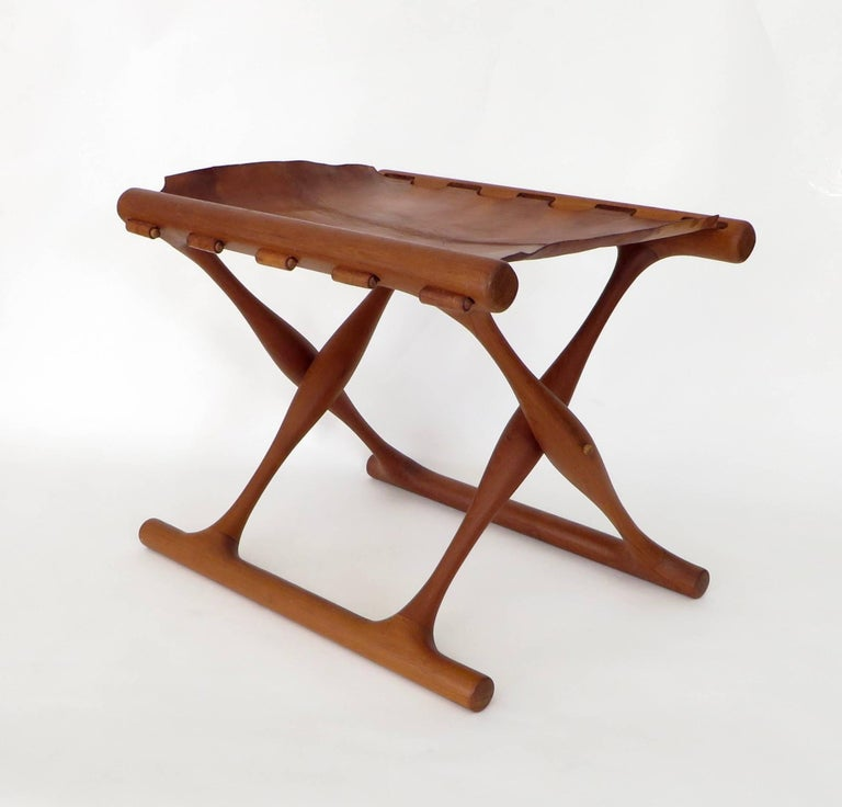 Folding stool by Poul Hundevad, Denmark, circa 1950. Sculptural solid teak frame with it's original leather seat. Frame is in excellent condition with no breaks or repairs. All the wooden pegs that hold leather are in place. Leather seat is heavily