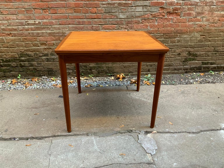 Great small space designed teak extension table by Poul Hundevad. Fully signed on bottom. Nice, simple ebonized tabletop detail, circa 1970. Very good original condition. Slight color variation between tabletop and hidden leaves.  Overall