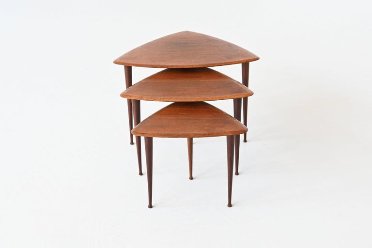 Beautiful shaped set of three nesting tables in the manner of Poul Jensen by Selig, Denmark 1960. These very nice triangle shaped tables are made of teak wood, the feet are solid and the tops are veneered. They give a minimalist look due to the
