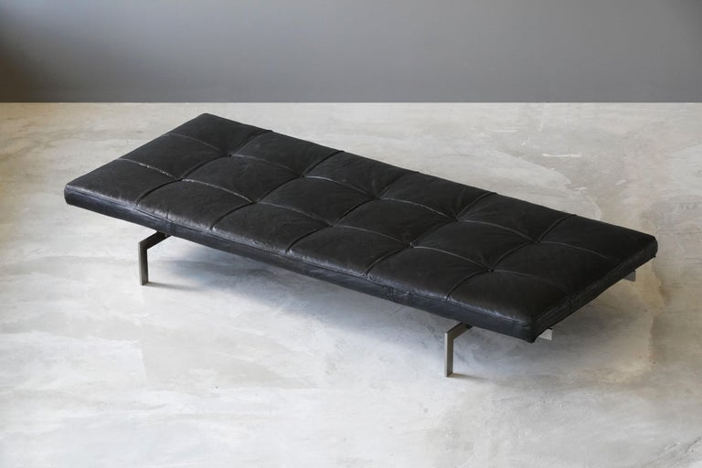 An early daybed designed by Poul Kjaerholm in 1957. Produced by E Kold Christensen, 1960s. Produced in leather, stainless steel, painted plywood, and rubber. Frame impressed with the manufacturer's mark.  The PK80 daybed is perhaps one of