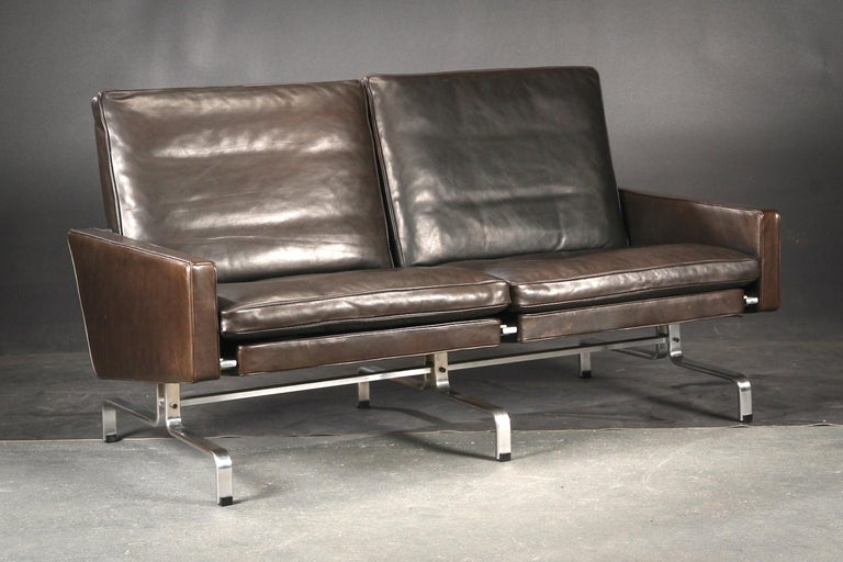 A two-seat sofa designed by Poul Kjaerhom and edited by Kold Christensen in 1958. Stamped.Frame in chromed steel. Back, sides and loose cushions upholstered in original black