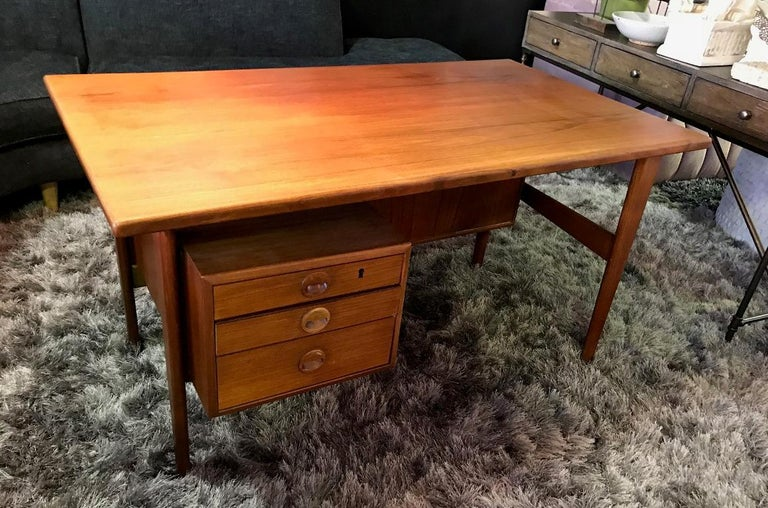 A stunning combination in beautiful vintage condition. Designed by Kai Kristiansen and made by Povl Dinesen. Wonderfully crafted and designed (with three front drawers and two storage compartments at backside) from solid teak. This desk and chair