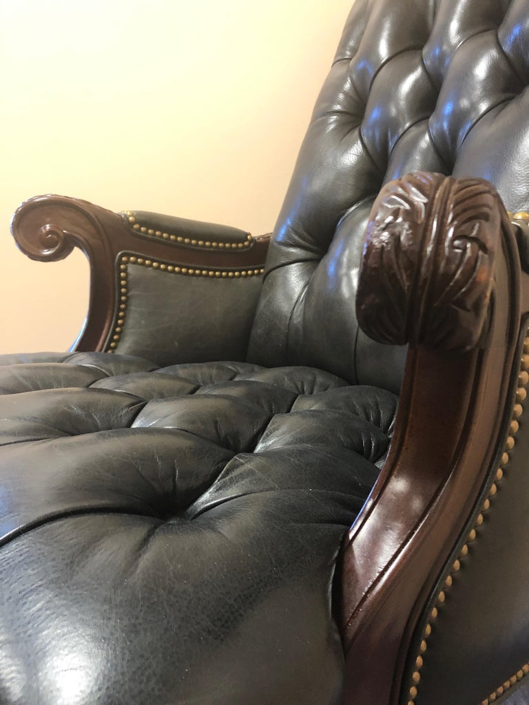 Very rich looking dark charcoal tufted leather executive chair having carved mahogany arms and swivel base on brass casters. Great looking from every angle. Measures: Arm height 29 seat depth 21.