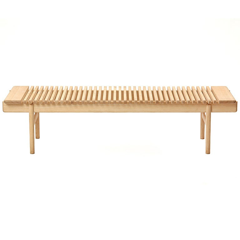 The PP589 bar bench in ash with slats resting on running rails. Each bar bench is made to order and takes between 16-24 weeks to produce. Available in oak or ash with soap or oil finish. Price varies with material and finish selection.