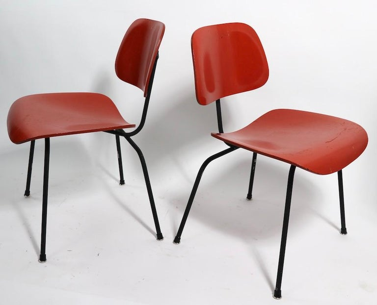 Pair of Eames designed DCM (Dining Chair Metal). Chairs This pair of chairs are currently in later, but not new, orange paint finish, the metal frames are also in later black paint finish, and the feet glides are later replacements. While the paint