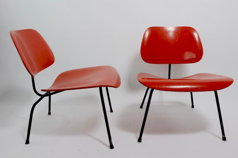 Iconic pair of Eames for Herman Miller LCM's in later orange and black paint finish. These chairs are structurally sound and sturdy, both have a later, but not new, orange paint surface on the wood seats and backs, and the metal frames are in later