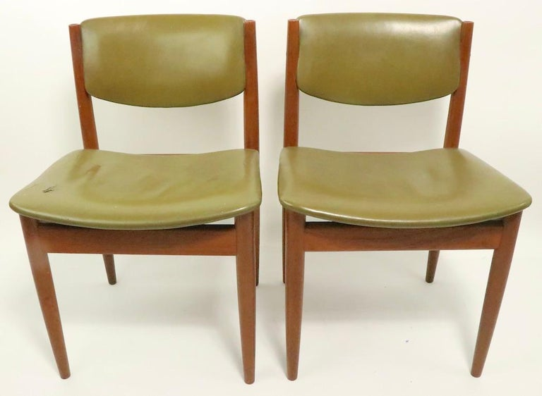 Architectural pair of teak and leather dining chairs designed by Finn Juhl for France and Son, model 197, circa 1960s. Both chairs are structurally sound and sturdy, both show wear to upholstery, please see images. Offered and priced as a pair,