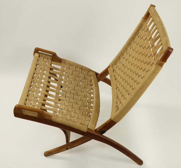 Pair of chic architectural folding scissor chairs made in Italy after the original Wegner design. These chairs have solid wood frames, woven rope seats and backs, and brass hardware. Both are in overall very good, original condition, one shows