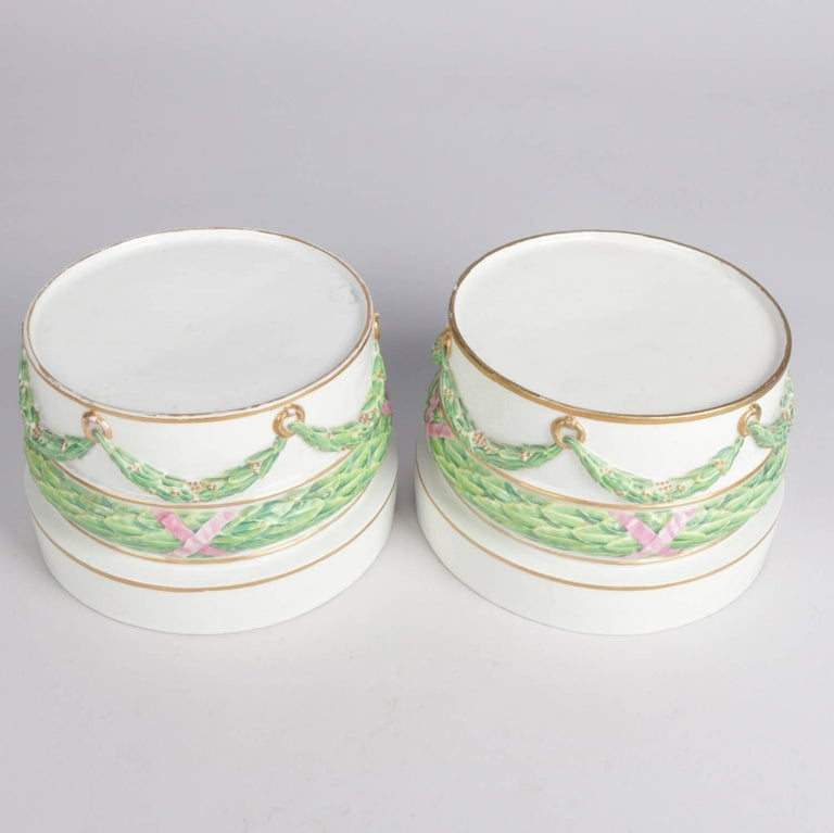 Pair of German porcelain round sculpture plinths/bases feature hand-painted and gilt draped garland decoration, en verso blue crossed sword mark and
