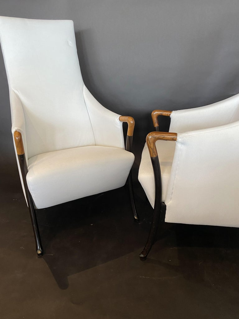 Set of 4 available, can sell as pairs for 11000 per pair. The high upholstered back and seat, with sweeping walnut arms and handrests, over splayed ebonized legs. Umberto Asagno started working for Giorgetti in 1968, and became head designer and