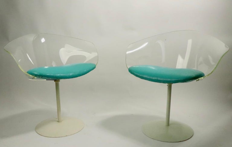 Stylish pair of swivel chairs each having a curved Lucite back with vinyl pad seat, mounted on a pedestal base. Both are in very good, clean original condition, showing slight cosmetic wear to white paint finish on bases, normal and consistent with