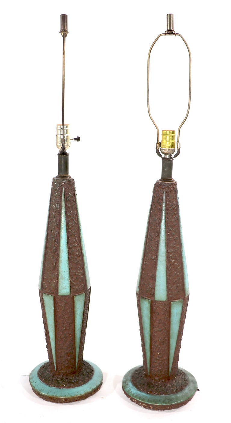 Stylish pair of Mid-Century table lamps having textured ceramic surfaces with smooth glaze triangular panels. The textured ground is a bronze / brown tone, the triangular panels are turquoise in color Both are in good original working condition,