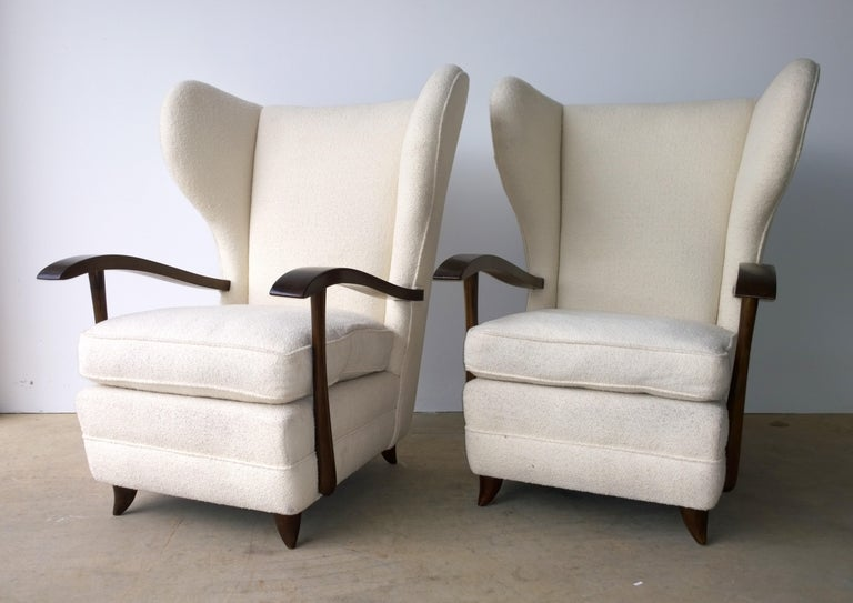 Offered is a pair of Mid-Century Modern Italian Paola Buffa attributed arm or lounge chairs with mahogany sculptural arms and upholstered in a white wool bouclé. The pair was purchased with the upholstery intact. Most likely the upholstery was