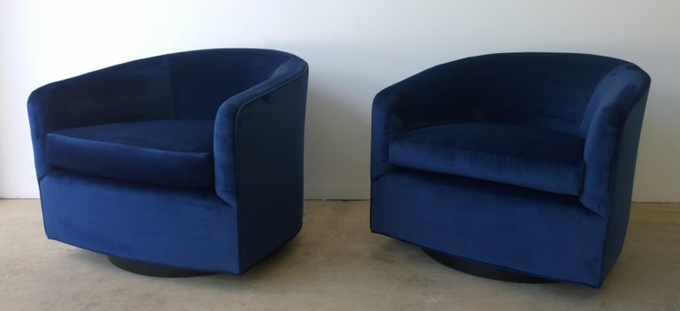 Offered is a pair of Mid-Century Modern Milo Baughman style swivel chairs with ebony wood veneer base upholstered in a new sapphire blue cotton velvet. This pair of swivel chairs exudes luxury in style, material and color. The comfort and proportion