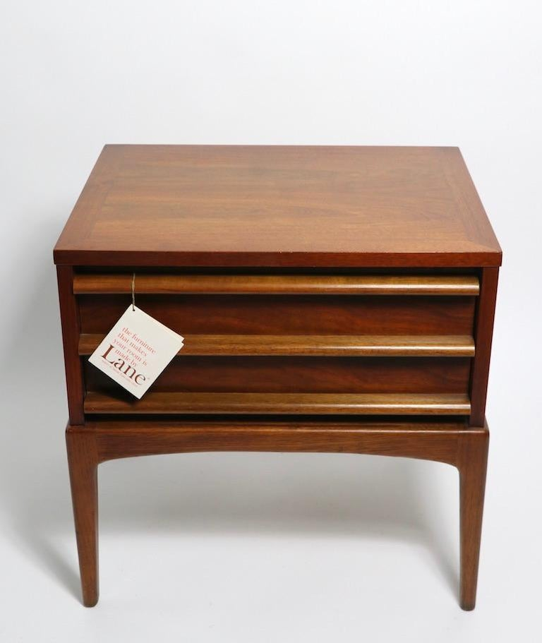 Stylish midcentury night tables, rhythm by Lane Furniture. Architectural design, American made in the Danish modern style. Constructed of solid walnut, having one deep drawer with three horizontal wood elements on the front. These nightstands still
