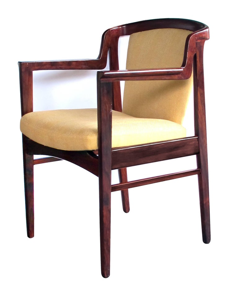 A good pair of Danish modern 1960s rosewood arm chairs in the manner of Kai Kristiansen; each with sculptural profile, the incurved back with padded splat above a tight seat flanked by knife-blade arms; all raised on tapering supports; with new