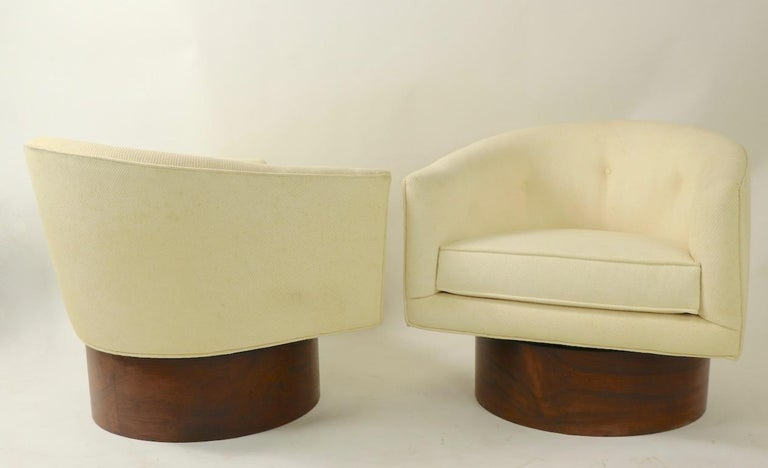 Exquisite pair of swivel chairs designed by Milo Baughman for Thayer Coggin. The upholstered chairs are mounted on exaggerated scale rosewood (veneer) plinth bases. Well crafted and superb design, sophisticated and chic pair of chairs by recognized