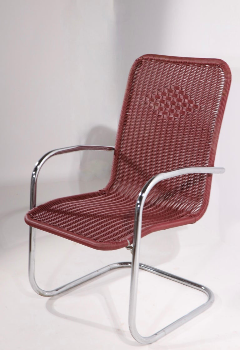 Pair of cantilevered lounge chairs having tubular chrome frames and continuous plastic wicker style woven seats and backs. Very chic design, manufacture attributed to Lloyd Loom, unsigned. Both show some wear, blemishing, and loss to chrome plating,
