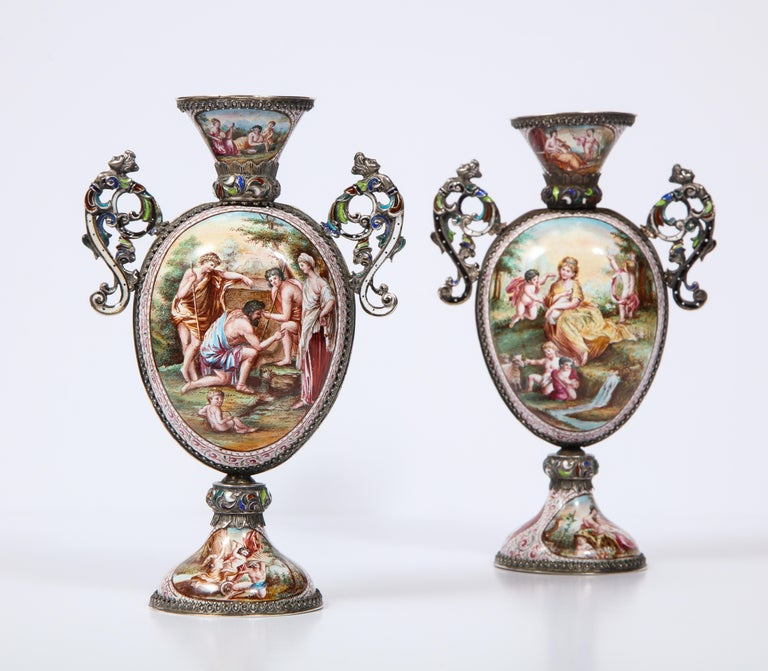 A beautifully pair of Viennese poly-chrome enamel on silver vases with mythological scenes and signed hallmarks: HB. There are a total of twelve panels, six on each vase, and each panel is exquisitely hand painted in multicolored poly-chrome enamel