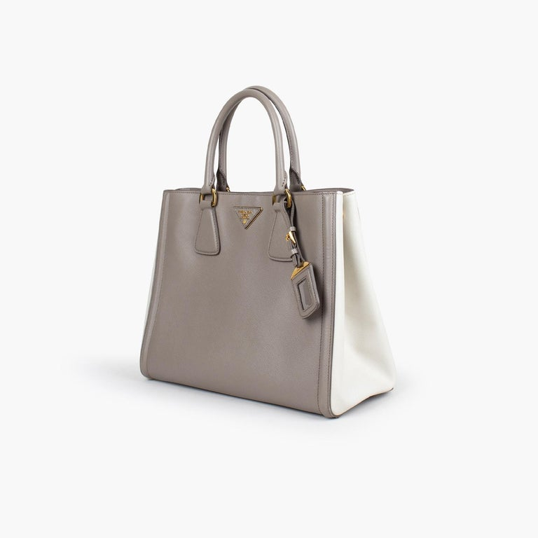 Grey and Cream Bicolor Saffiano Lux leather Prada tote with  - Brass hardware - Dual rolled top handles - Single detachable flat adjustable shoulder strap - Logo placard at face - Protective feet at base, tonal logo jacquard lining, five interior