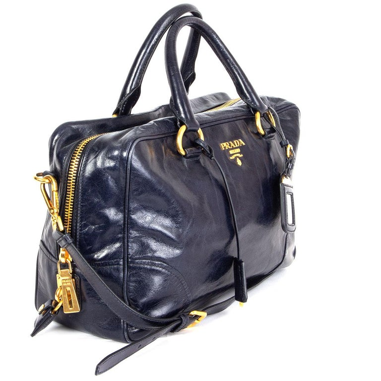 100% authentic Prada Medium Bauletto Bag Vitelli in midnight blue shiney leather featuring gold-tone hardware. Opens with a zipper on top and is lined in midnight blue signature nylon with one zipper pocket against the back with an open pocket