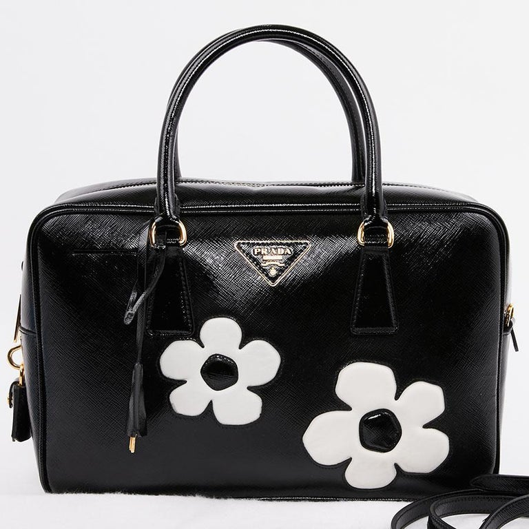 Magnificent second-hand PRADA bag in black patent Saffiano leather with two large inlaid white flowers on each side. It has a zipper. The lining is in