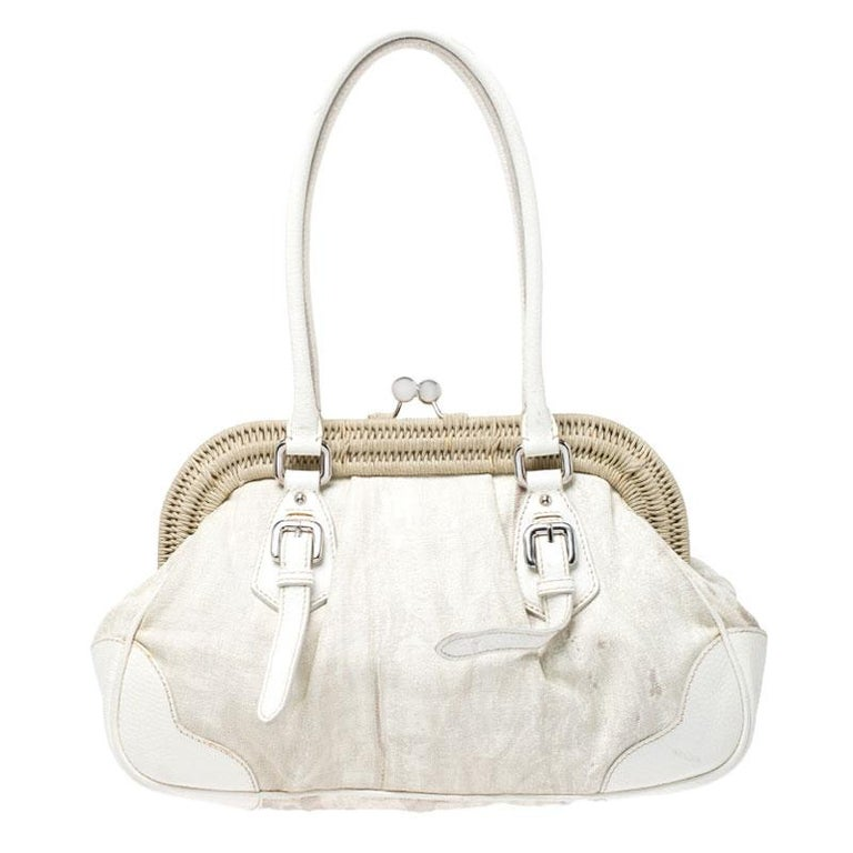 This exquisitely designed satchel by Prada is the right choice for the woman of today. An epitome of fashion, this beautifully crafted bag comes with a canvas and leather exterior, dual handles, a kiss lock that opens to a nylon interior with a zip