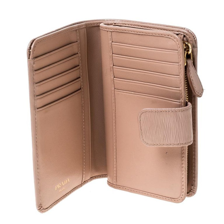Stay organised in style with this wallet from Prada. It is crafted from leather and it features a zip compartment and a snap button that leads to multiple slots and open compartments. The wallet is compact and durable.  Includes: Original Box,