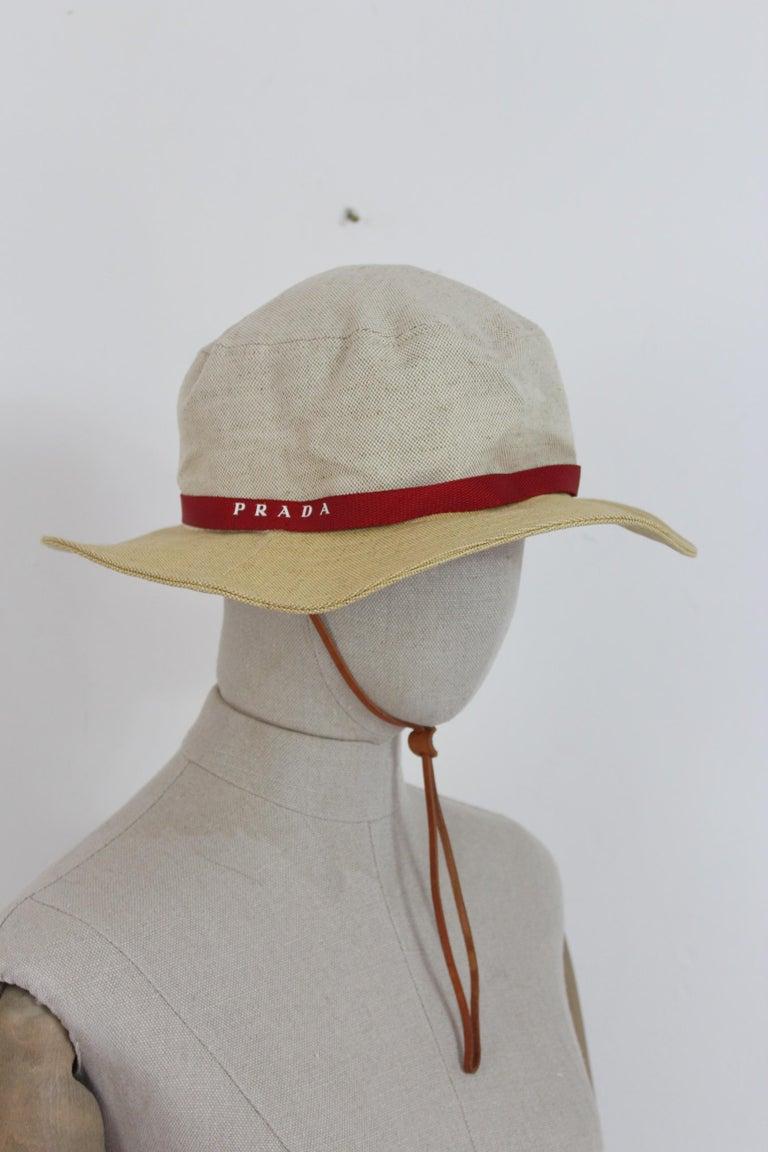 Prada vintage 90s unisex hat. Cowboy model, adjustable leather neck strap. Beige color and red details, 52% linen 48% cotton. Made in Italy. Excellent vintage conditions.  Size: L.  Diameter: 18 cm