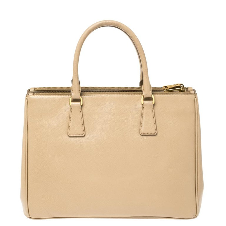 Feminine in shape and grand on design, this Double Zip tote by Prada will be a loved addition to your closet. It has been crafted from beige Saffiano Lux leather and styled minimally with gold-tone hardware. It comes with two top handles, zip