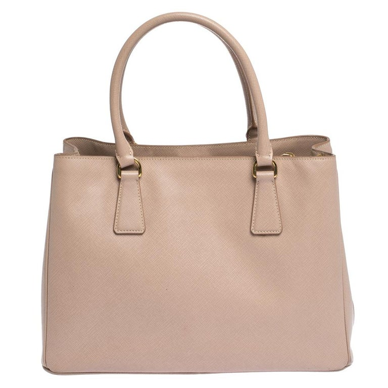 This Galleria tote by Prada will be a loved addition to your closet. It has been crafted from Saffiano Lux leather and styled minimally with gold-tone hardware. It comes with two top handles and a perfectly-sized main compartment. The bag is