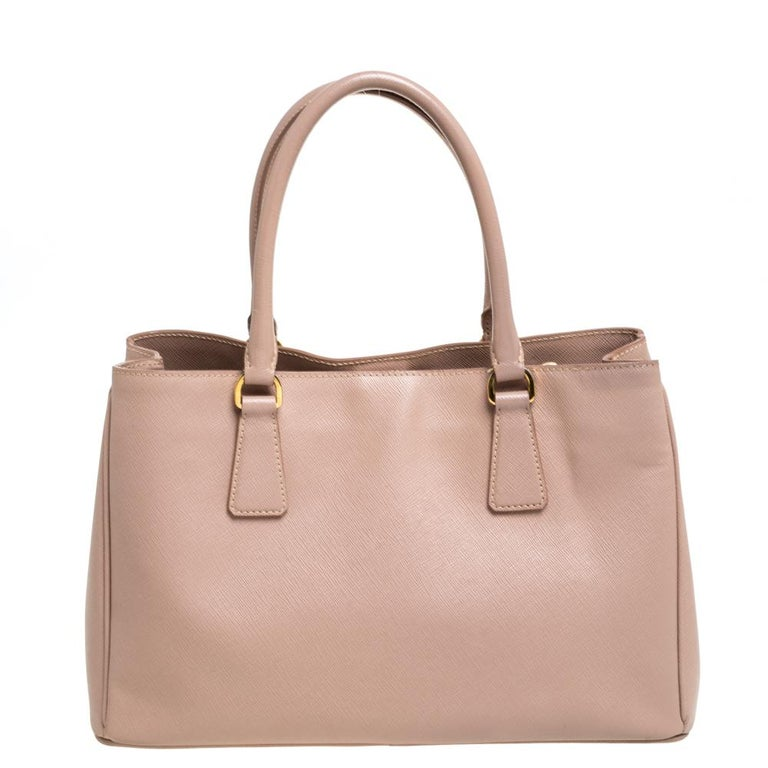 Feminine in shape and grand on design, this Zip tote by Prada will be a loved addition to your closet. It has been crafted from leather and styled minimally with gold-tone hardware. It comes with two top handles and a nylon-lined interior housing a