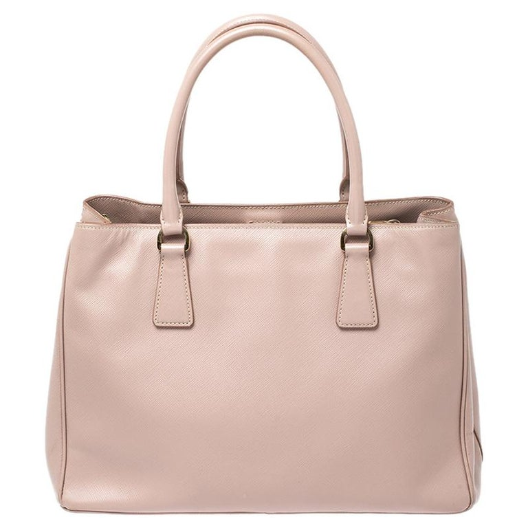 Sophisticated and timeless, this practical Saffiano Lux tote by Prada was made for daily use. Crafted from Saffiano leather in a beautiful shade of beige, the exterior features a Prada logo emblem at the front, rolled double top handles, a gold-tone