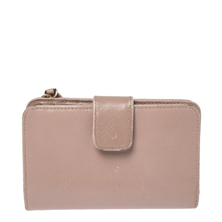 A compact and practical option to store your handy essentials, this Zip Around Compact wallet from Prada is crafted from beige Saffiano Lux leather. It has a zip-around and button closure, the brand logo on the front and is equipped with multiple
