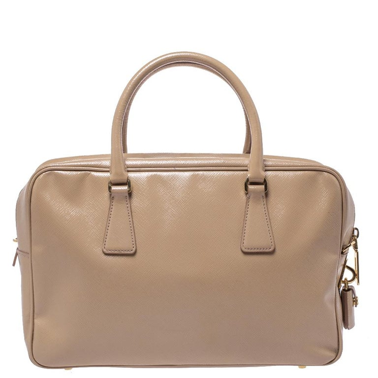 When you carry this Prada creation, be ready to catch admiring glances as this bag is stylish and handy. The bag has been crafted from patent leather in a lovely black shade and designed with two top handles. The top zip closure opens to a