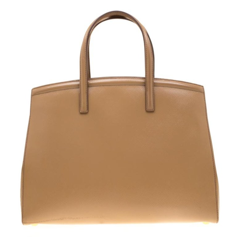 This stunning tote is high on appeal and style. Dazzling in a gorgeous beige shade, the bag is crafted from Saffiano patent leather and features two top handles. The snap button leads way to a fabric-lined interior with enough space for your